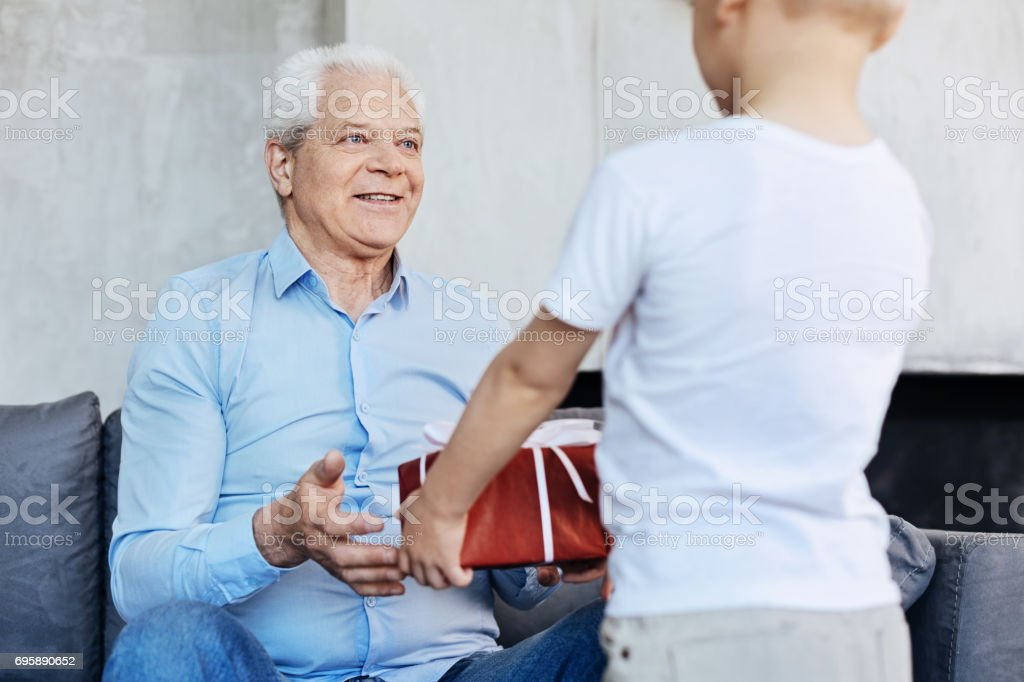 Excited Elderly Man Receiving A Present Royalty Free Stock Photo