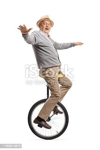 Full length shot of an excited elderly man riding a unicycle isolated on white background