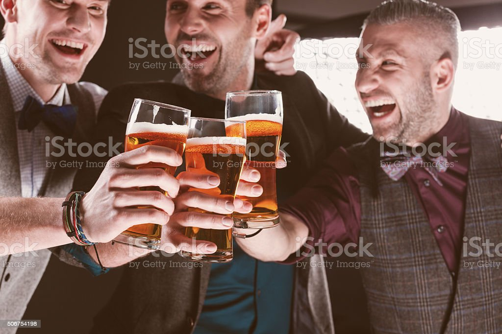 Excited elegant businessmen toasting with beer in nightclub stock photo