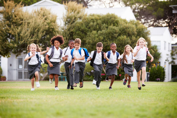 excited elementary school pupils wearing uniform running across field at break time - униформа стоковые фото и изображения