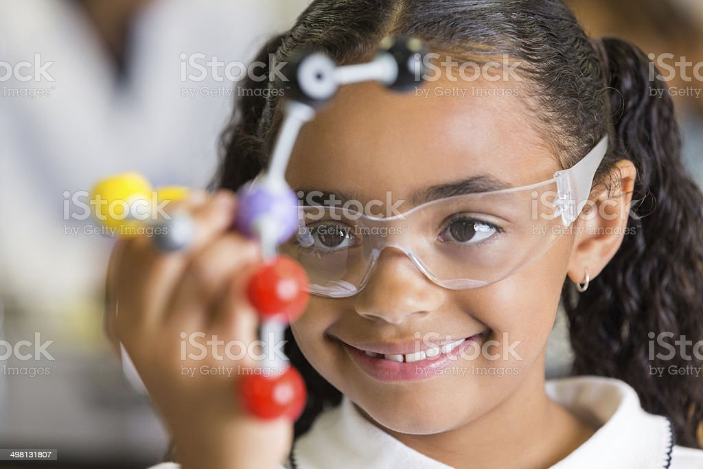 Excited elementary school student using atom model in science class stock photo