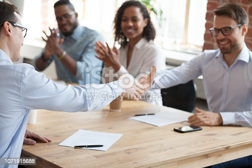 istock Excited employees handshake at meeting after successful negotiations 1071915688