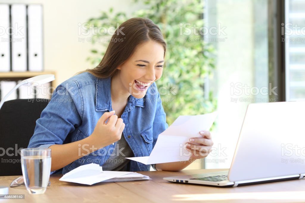 Excited entrepreneur girl reading a letter stock photo