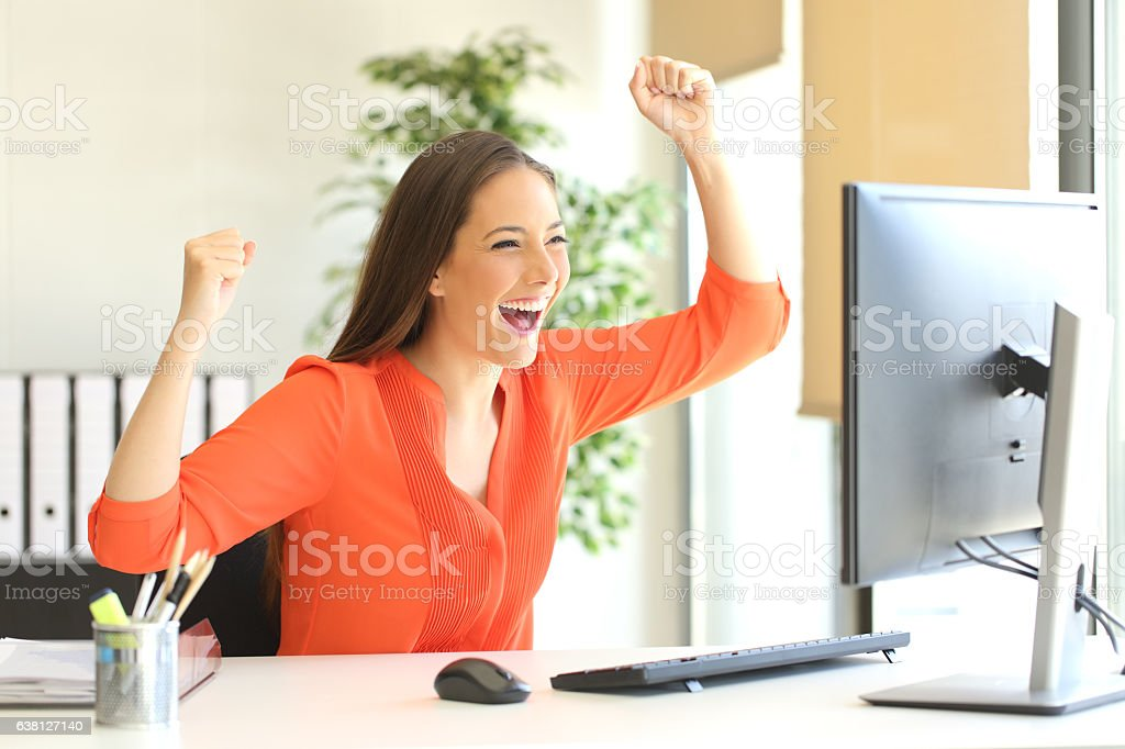 Excited entrepreneur watching computer monitor stock photo
