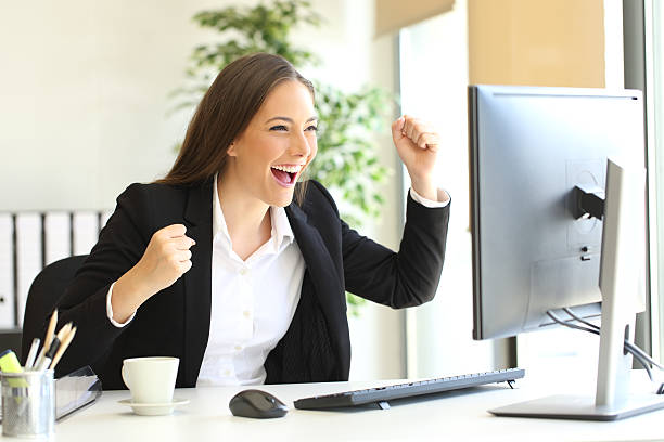 Excited executive watching a computer monitor stock photo