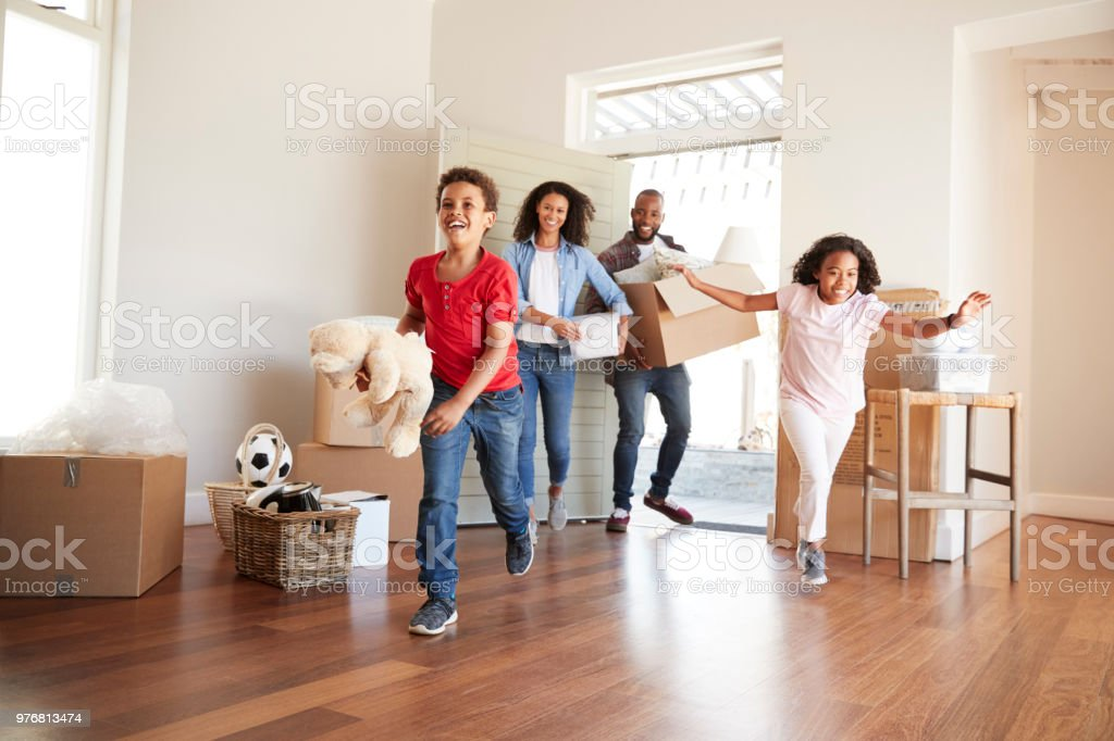 Excited Family Carrying Boxes Into New Home On Moving Day stock photo