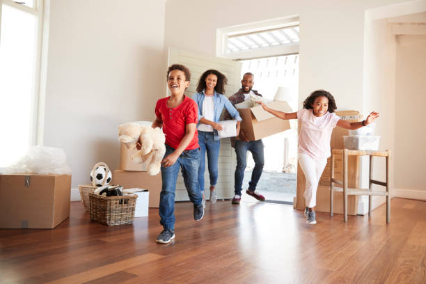 excited family carrying boxes into new home on moving day - house hunting stock photos and pictures