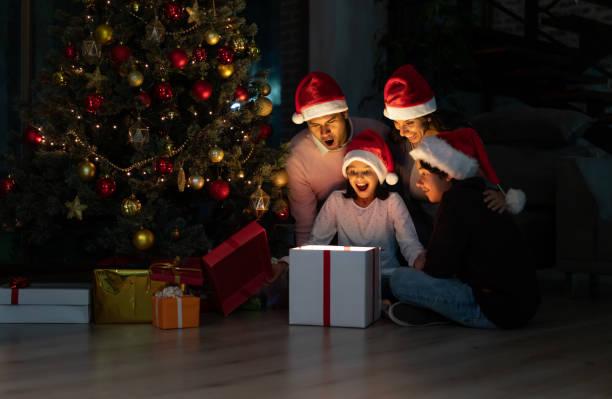 Aufgeregte Familie öffnet Weihnachtsgeschenke zu Hause – Foto