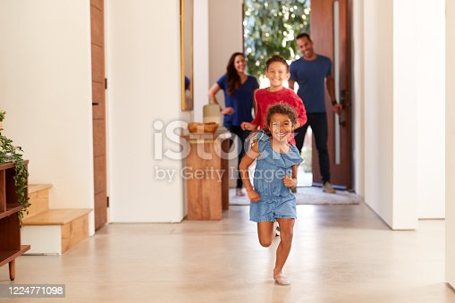 670900812 istock photo Excited Family Returning Home After Trip Out With Children Running Through Front Door 1224771098