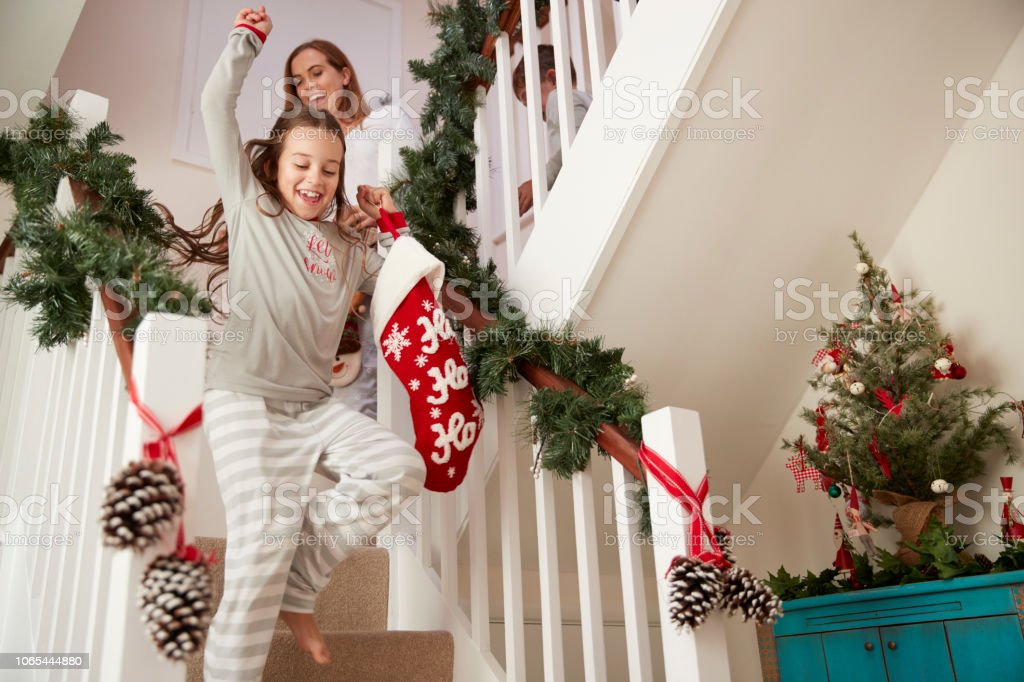Excited Family Wearing Pajamas Running Down Stairs Holding Stockings On Christmas Morning stock photo