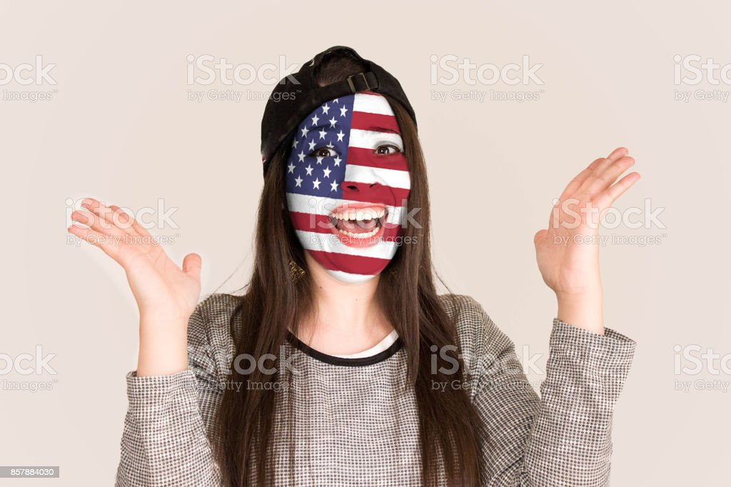 Excited fan USA in face paint cheering against USA  flag stock photo