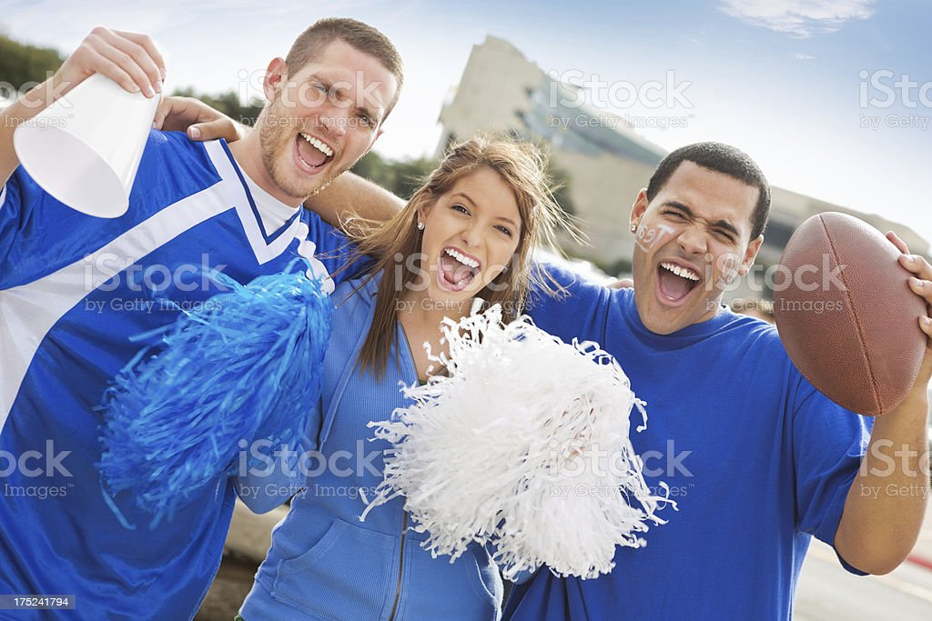 Excited fans at tailgate party cheering near football stadium stock photo