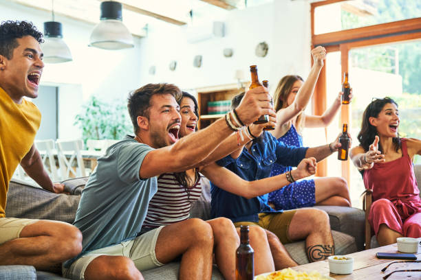 Excited fans shouting while watching match on TV stock photo