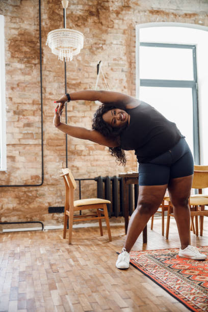 Excited fat woman exercising at home stock photo stock photo