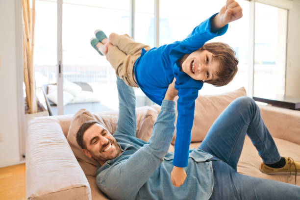 Excited father and son enjoying time together during lockdown stock photo