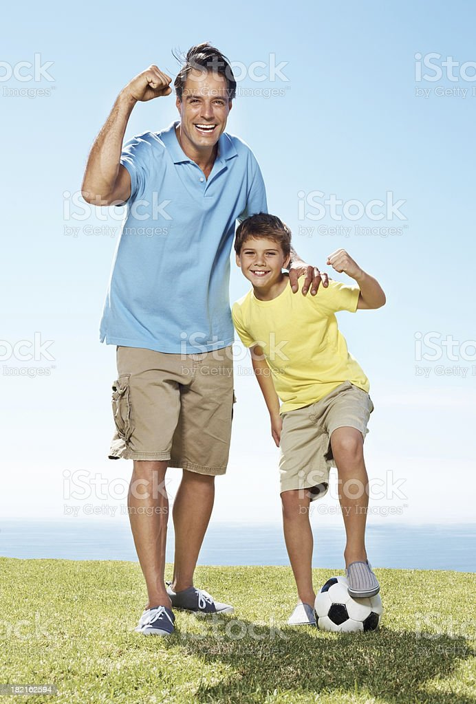 Excited father and son standing outside with a football royalty-free stock photo
