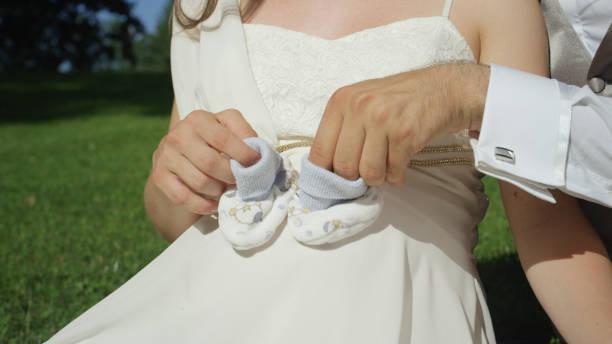 close up: aufgeregt vater mit einem paar babysocken über ihren schwangeren bauch - hochzeitsspiele eltern stock-fotos und bilder