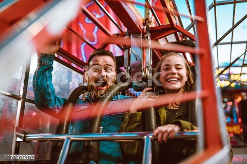 Excited Female And Scared Male On A Rollercoaster Ride In Theme Park