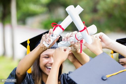 istock Excited female college grads proudly hold up diplomas 614225382