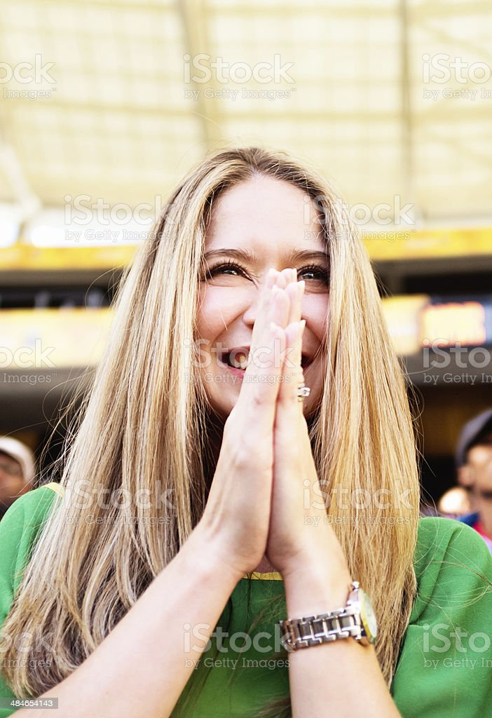Excited female fan at soccer match looks delighted stock photo