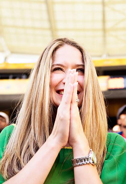 glücklich weibliche fan im fußballspiel looks erfreut - spielerfrauen stock-fotos und bilder