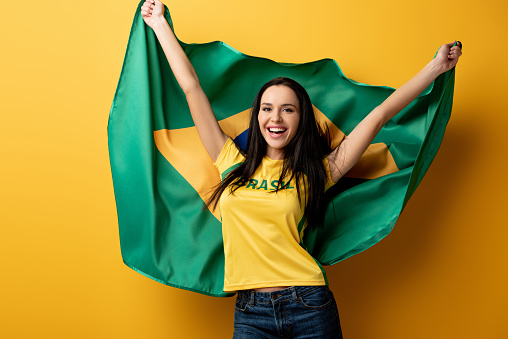 excited female football fan holding brazilian flag on yellow