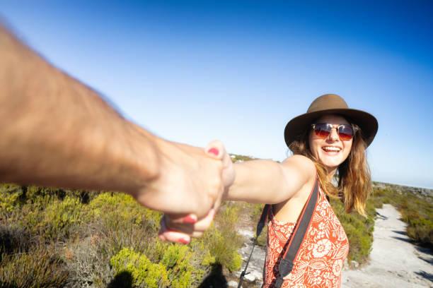 Aufgeregte Frau zieht ihren männlichen Freund an der Hand, die ihn führt – Foto
