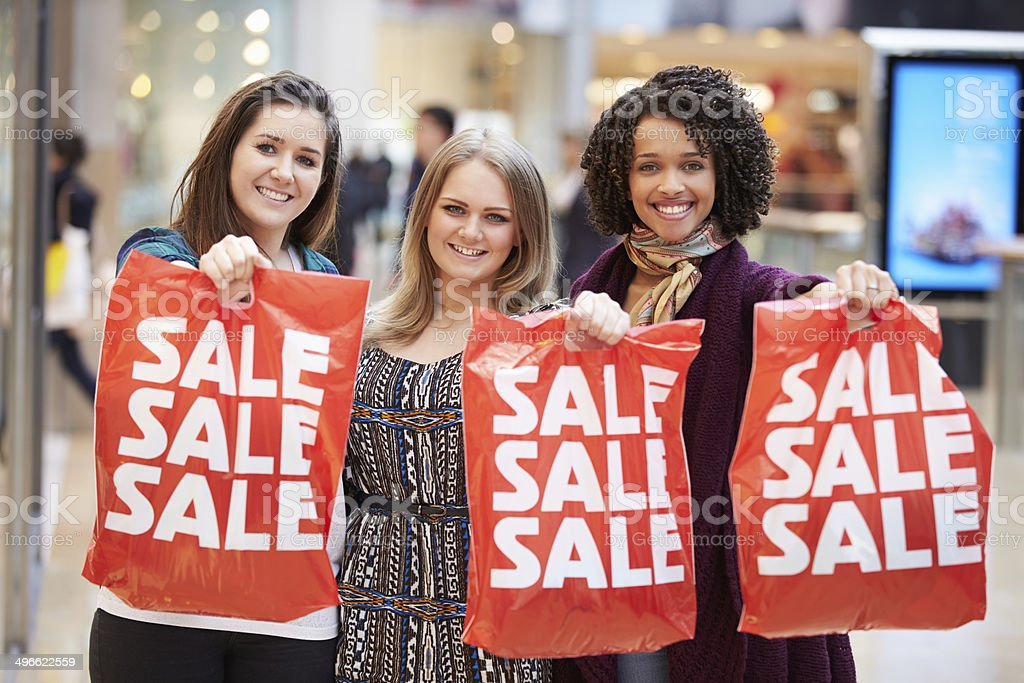 Excited Female Shoppers With Sale Bags In Mall royalty-free stock photo