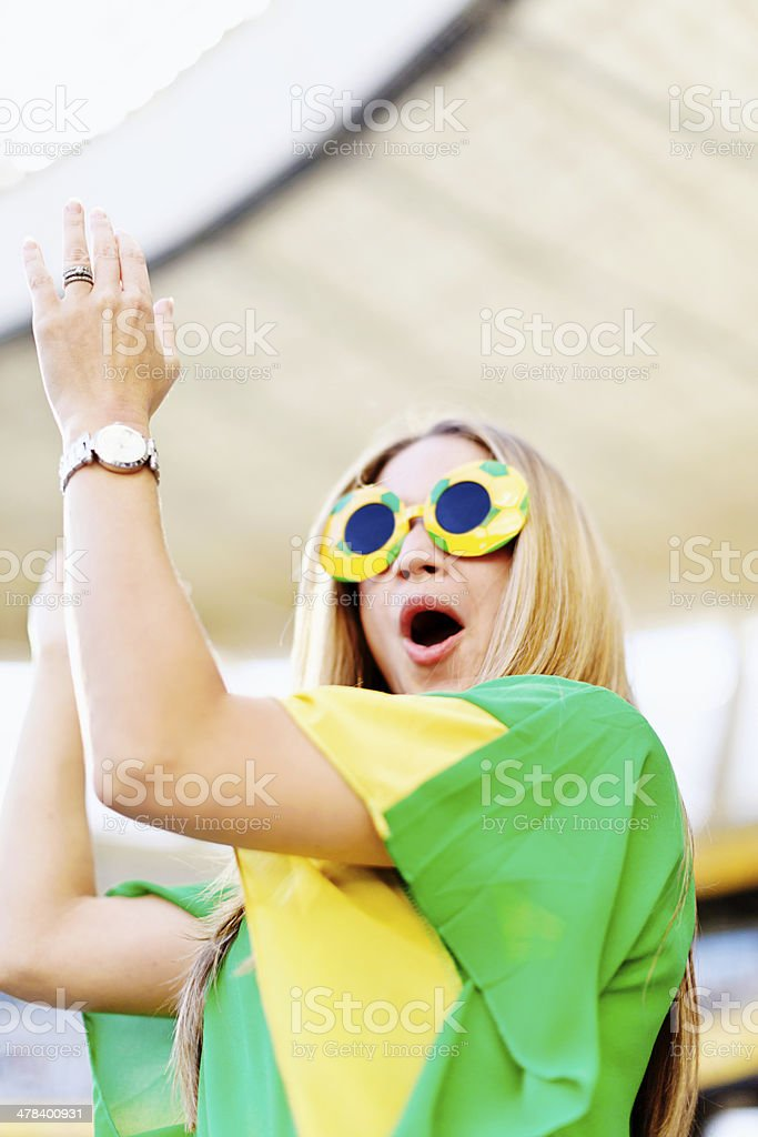 Excited female soccer fan cheers her team stock photo