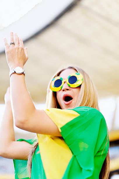 glücklich weibliche fußball-fan cheers ihr team - spielerfrauen stock-fotos und bilder