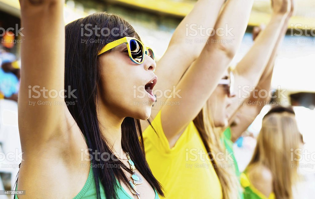 Excited female soccer fans wave their arms in the air royalty-free stock photo
