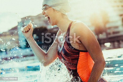 Excited female swimmer with clenched fist celebrating victory in the swimming pool. Woman swimmer cheering success in pool wearing swim goggles and cap.