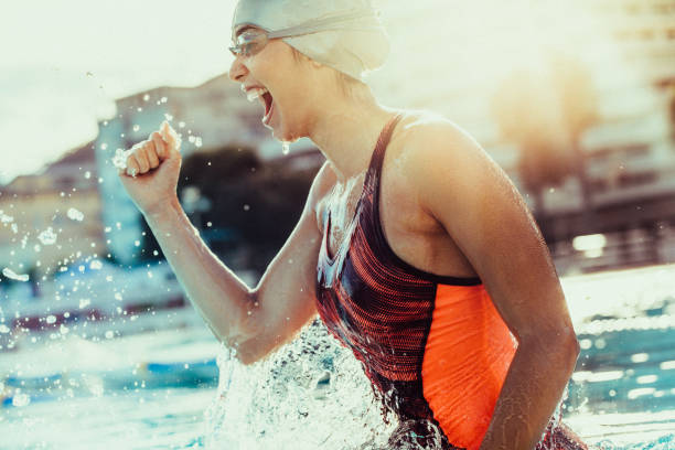 excited female swimmer celebrating victory - sportsmenka zdjęcia i obrazy z banku zdjęć