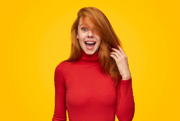Excited female touching hair Lovely young woman in red turtleneck sweater touching ginger hair and looking at camera with amazed face expression while standing on vibrant yellow background hand in hair stock pictures, royalty-free photos & images