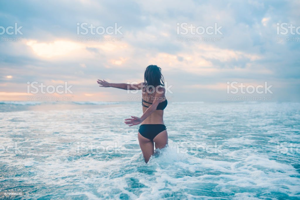 Excited Female with Raised Arms Goes Toward Wavy Ocean stock photo