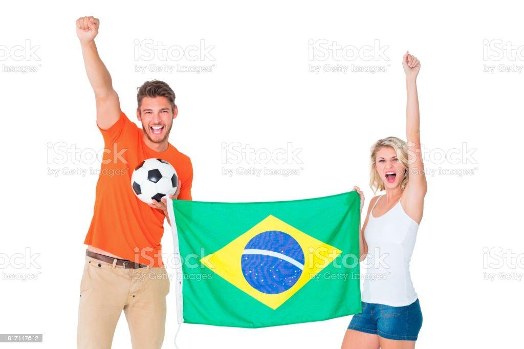 Feliz casal de futebol com bandeira do Brasil - foto de acervo