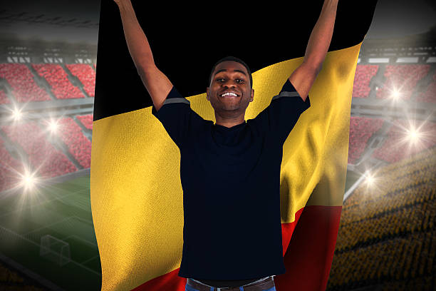 Excited football fan in black cheering holding belgium flag stock photo