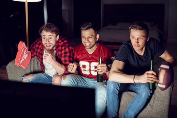 opgewonden voetbalfans amerikaans voetbal kijken in de avond - football friends tv night stockfoto's en -beelden