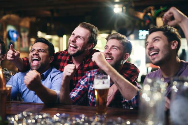 Aufgeregte Fußballfans beobachten Fußball in der Kneipe – Foto