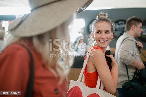 Young woman is talking excitedly to her mother while they are on their way to board a flight at an airport.