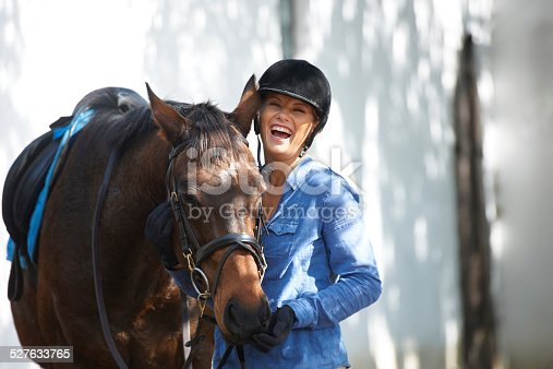 An attractive woman laughing outside while standing outside with her horse