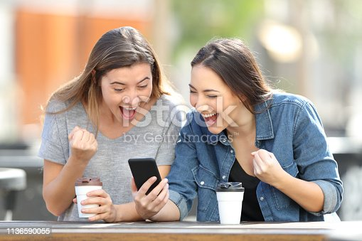 istock Excited friends celebrating online news on phone 1136590055