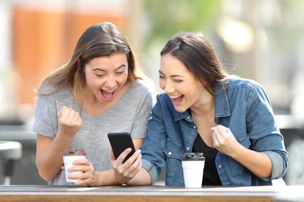 aufgeregte freunde feiern online-news am telefon - die besten apps stock-fotos und bilder