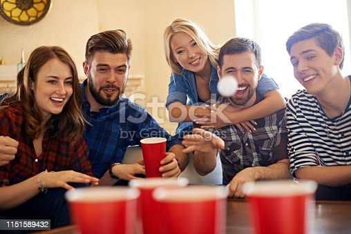 Laughing men and women gathering at home and playing beer pong game together
