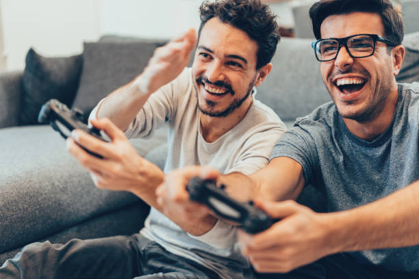 Excited friends playing video games Excited friends playing video games at home brother stock pictures, royalty-free photos & images