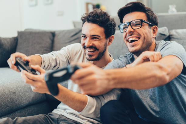 Excited friends playing video games stock photo