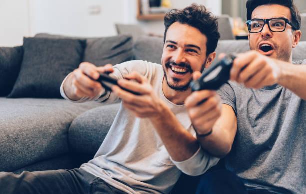 excited friends playing video games - man joystick imagens e fotografias de stock