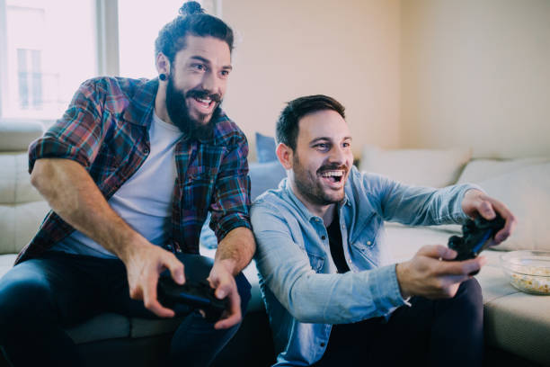 Excited friends playing video games Gamers playing video games together from home man bun stock pictures, royalty-free photos & images
