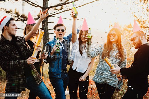 Attractive young people raising glasses of beer and exploding confetti crackers during Christmas celebration in countryside