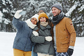 istock Excited friends taking selfie in winter forest 1057945622